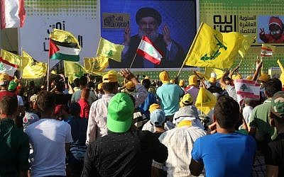 Young men hold Lebanese national flags and yellow flags of the Lebanese Shiite terror group Hezbollah as they watch its leader Hassan Nasrallah deliver a speech on a screen in the southern Lebanese town of Bint Jbeil on August 13, 2016 during a commemoration marking the tenth anniversary of the end of the Second Lebanon War. (AFP Photo/Mahmoud Zayyat)