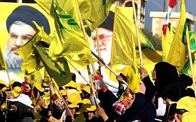 Women wave a Lebanese national flag and Hezbollah flags in front of portraits of Iran's supreme leader Ayatollah Ali Khamenei (R) and Hezbollah leader Hassan Nasrallah, in the southern Lebanese town of Bint Jbeil on August 13, 2016. (AFP Photo/Mahmoud Zayyat)