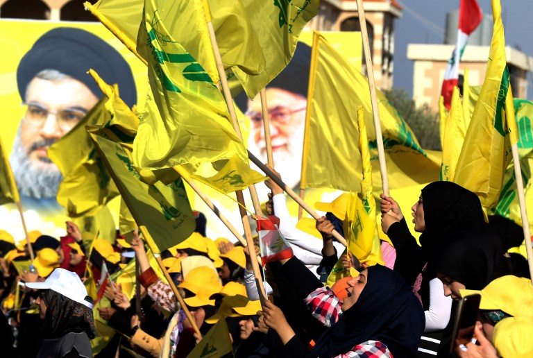 Women wave a Lebanese national flag and Lebanese Shiite movement Hezbollah flags in front of portraits of Iran's supreme leader Ayatollah Ali Khamenei (R) and Hezbollah leader Hassan Nasrallah, in the southern Lebanese town of Bint Jbeil on August 13, 2016, during a commemoration marking the tenth anniversary of the end of the war between Hezbollah and Israel. (AFP PHOTO / MAHMOUD ZAYYAT)