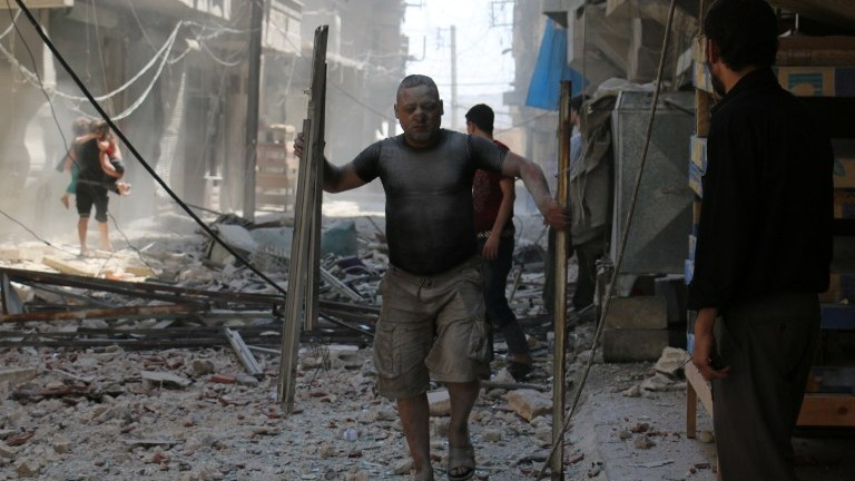 A Syrian man covered with dust carries pieces of metal on a street cluttered with rubble following a reported air strike on the rebel-held neighbourhood of Sakhur in the northern city of Aleppo, on August 15, 2016. (AFP PHOTO / AMEER ALHALBI)