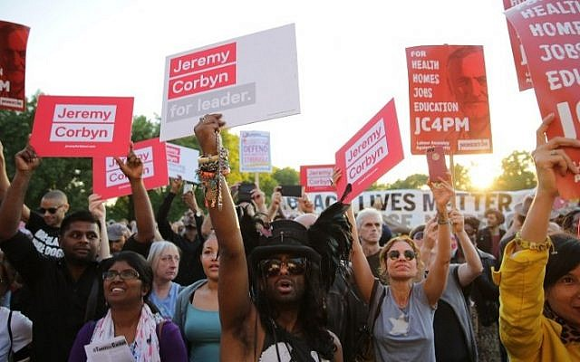 Supporters of Jeremy Corbyn hold up placards and cheer at a Black, Asian and minority ethnic (BAME) rally in north London on August 15, 2016. (AFP PHOTO / DANIEL LEAL-OLIVAS)