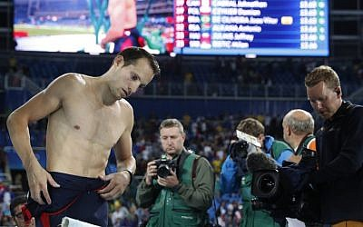 France's Renaud Lavillenie, left, looks dejected after he placed second in the Men's Pole Vault Final during the athletics event at the Rio 2016 Olympic Games in Rio de Janeiro, August 15, 2016.  (AFP/Adrian DENNIS)