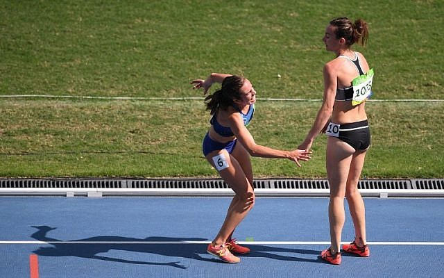 New Zealand's Nikki Hamblin, right, helps USA's Abbey D'agostino after she was injured in the Women's 5000m Round 1 during the athletics event at the Rio 2016 Olympic Games, Rio de Janeiro, August 16, 2016.  (AFP/Johannes EISELE)