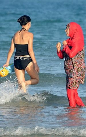 """Women, one, wearing a """"burkini"""", a full-body swimsuit designed for Muslim women, walk in the water on Ghar El Melh beach near Bizerte, north-east of the capital Tunis, August 16, 2016. (AFP/FETHI BELAID)"""