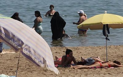 2 Muslim women wearing a chador as they enjoy their time with other people  a beach of Narbne, southern France, June 4, 2015. (AFP/Raymond ROIG)