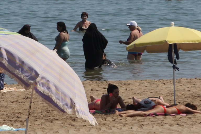 cae9fead67d 2 Muslim women wearing a chador as they enjoy their time with other people a  beach
