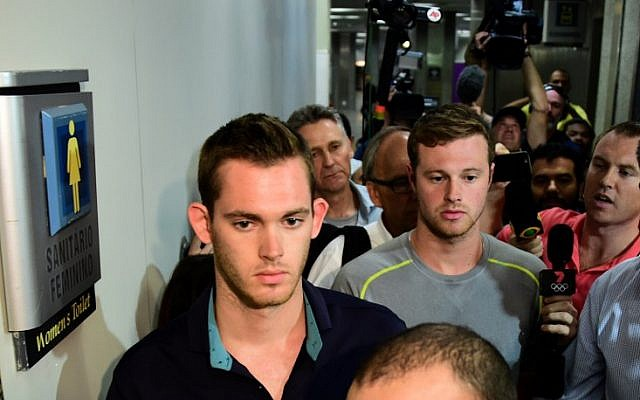 American swimmers Gunnar Bentz (L) and Jack Conger leave the police station at the Rio de Janeiro International Airport after being detained on the plane that would travel back to the US.  (AFP PHOTO / TASSO MARCELO)