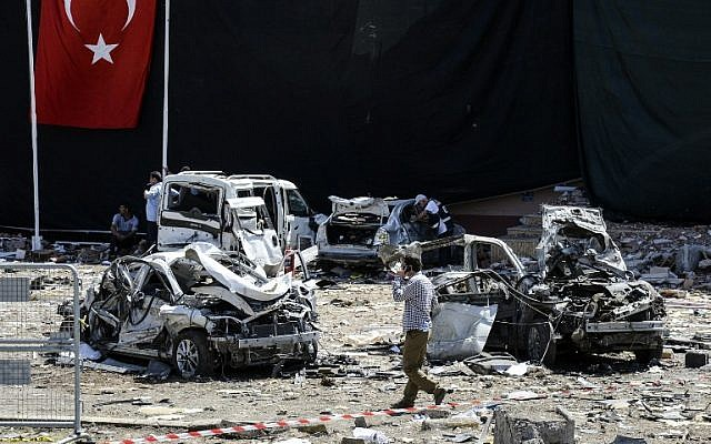A man walks among the wreckage of vehicles as Turkish rescue workers and police inspect the blast scene following a car bomb attack on a police station in the eastern Turkish city of Elazig, on August 18, 2016. (AFP PHOTO / ILYAS AKENGIN)