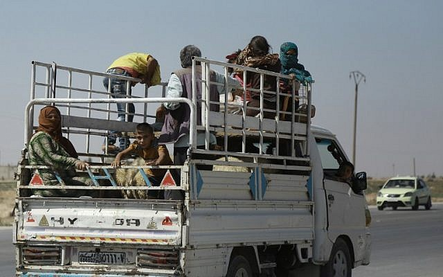Syrian Kurdish civilians board a truck as they flee reported shelling in the northeastern governorate of Hasakah, toward the city of Qameshli, August 18, 2016. (AFP/DELIL SOULEIMAN)