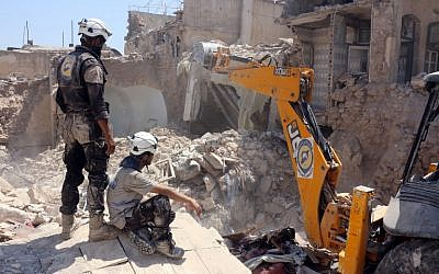 Syrian civil defense volunteers, known as the White Helmets, dig through the debris following an earlier airstrike in the Jallum neighborhood of Aleppo, on August 20, 2016. (AFP/Thaer Mohammed)
