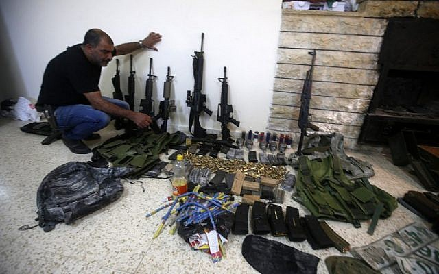 A member of the Palestinian security forces displays weapons at a police station in the West Bank city of Nablus , that the police found on search operation for gunmen who are on the run, August 21, 2016. (AFP/JAAFAR ASHTIYEH)