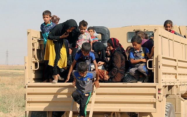 Iraqi displaced families step down from a truck upon their arrival in an area controlled by the Peshmerga forces, some 55 kilometers west of Iraqi city of Kirkuk, on August 21, 2016 after they left their northern village of Hawija to escape from Islamic State group jihadists. (AFP /Marwan IBRAHIM)