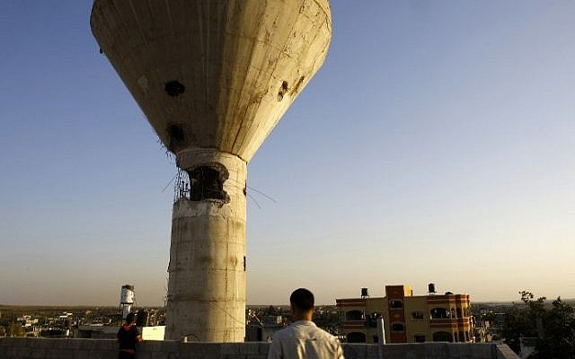 Palestinians look at a water tower that was first damaged during the 2014 Gaza war and appears to have again been struck by Israeli fire on August 21, 2016 in Beit Hanun in the northern Gaza Strip. (AFP PHOTO / MOHAMMED ABED)