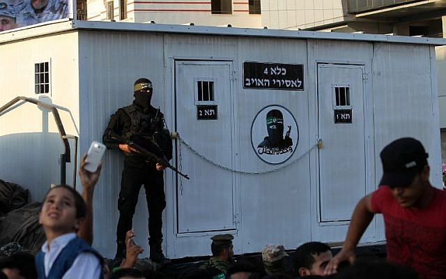"A member of the al-Qassam Brigades stands guard in front of a prefab made up to look like an Israeli prison during an anti-Israel military parade on August 21, 2016 in Rafah in the southern Gaza Strip. The sign reads in Hebrew ""Prison 4, for prisoners of the enemy."" (AFP/ SAID KHATIB)"