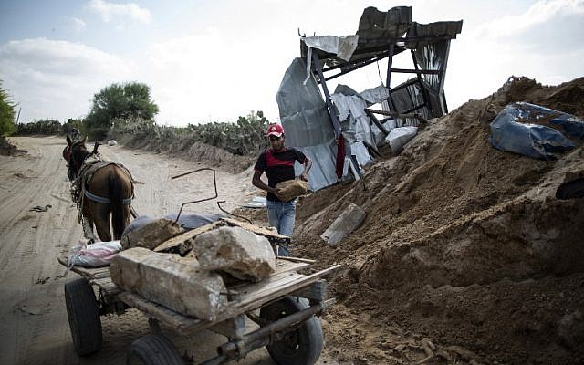 A Palestinian man loads stones on a cart next to a crater in Beit Lahia in the northern Gaza Strip on August 22, 2016, following an Israeli airstrike the night before that targeted Hamas positions in response to a rocket fired from the Palestinian enclave that hit the Israeli city of Sderot. (Mahmud Hams/AFP)