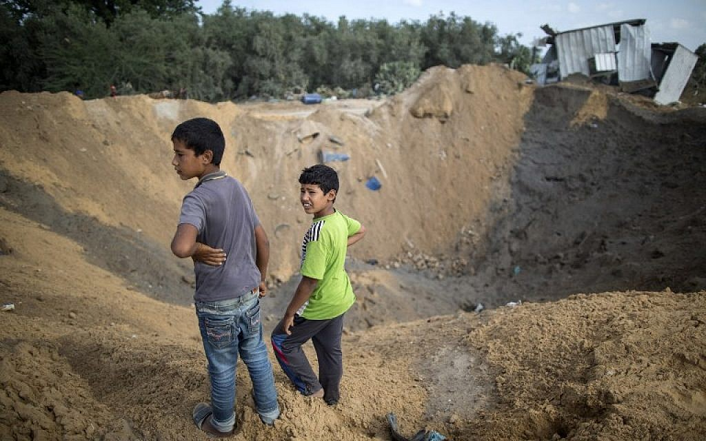 Illustrative. Palestinian children stand next to a crater in Beit Lahiya in the northern Gaza Strip on August 22, 2016, following an Israeli airstrike the night before that targeted Hamas positions in response to a rocket fired from the Palestinian enclave that hit the Israeli city of Sderot. (Mahmud Hams/AFP)