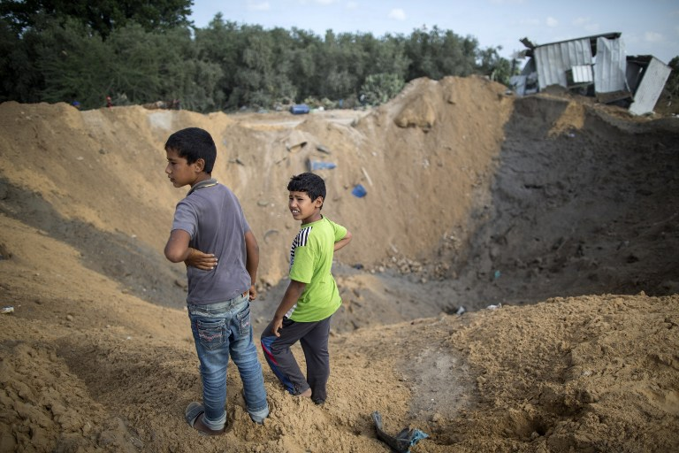 Palestinian children stand next to a crater in Beit Lahia in the northern Gaza Strip on August 22, 2016, following an Israeli airstrike the night before that targeted Hamas positions in response to a rocket fired from the Palestinian enclave that hit the Israeli city of Sderot. (Mahmud Hams/AFP)