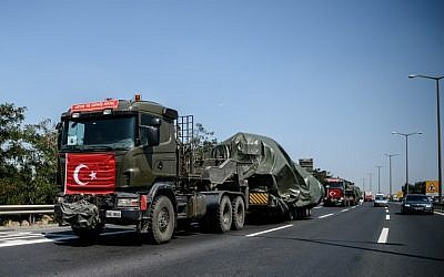 Military trucks with the Turkish national flag transport tanks as they drive on a highway out of Istanbul on August 22, 2016. (AFP/OZAN KOSE)