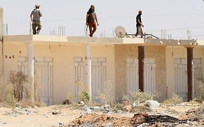 Libyan pro-government forces walk on the roof of a building in Sirte as they comb through residential neighborhoods taken from the Islamic State (IS) group on August 22, 2016. (AFP/Mahmud Turkia)