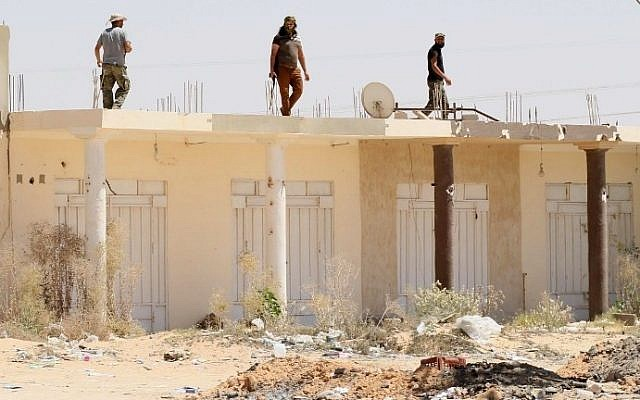 Libyan pro-government forces walk on the roof of a building in Sirte as they comb through residential neighborhoods taken from the Islamic State (IS) group on August 22, 2016. (AFP PHOTO / MAHMUD TURKIA)