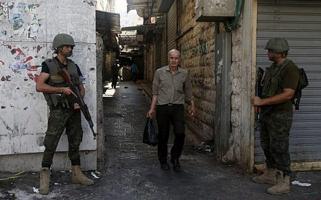 Members of the Palestinian security forces stand guard as they patrol the West Bank city of Nablus on August 23, 2016 during ongoing clashes between Palestinian gunmen and security forces. (AFP PHOTO / JAAFAR ASHTIYEH)