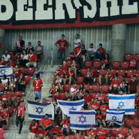 Hapoel Beersheba fans wave Israeli flags before the UEFA Champions League group stages play-off soccer match between Celtic and Hapoel Beersheba at the Turner Stadium in the southern Israeli city of Beersheba on August 23, 2016. (Gil Cohen-Magen/AFP)