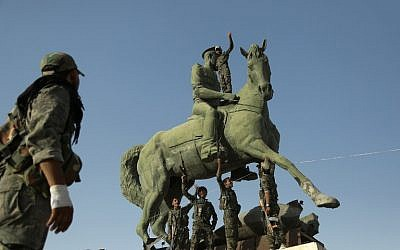 Kurdish fighters belonging to the police force -- the Asayesh -- and the People's Protection Units (YPG) stand on a statue of Basel Assad, the late elder brother of the Syrian President, in the northeastern Syrian city of Hasakeh on August 23, 2016, after they agreed to a truce with regime forces. (AFP PHOTO/DELIL SOULEIMAN)