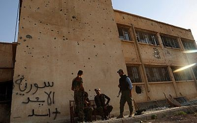 Kurdish fighters belonging to the local police force -- the Asayesh -- and the People's Protection Units (YPG) stand in front of a building covered in bullet holes in the northeastern Syrian city of Hasakeh on August 23, 2016, after they agreed to a truce with regime forces. (Delil Souleriman/AFP)