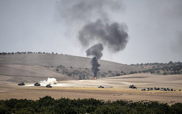 This picture taken from the Turkish Syrian border city of Karkamis in the southern region of Gaziantep, on August 24, 2016 shows Turkish army tanks and pro-Ankara Syrian opposition fighter trucks positioned two kilometers west from the Syrian Turkish border town of Jarablus. (AFP/ BULENT KILIC)