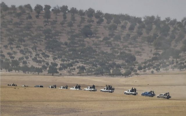 This picture taken from the Turkish Syrian border city of Karkamis in the southern region of Gaziantep, on August 24, 2016 shows pro-Ankara Syrian opposition fighter trucks positioned two kilometers west from the Syrian Turkish border town of Jarablus. (AFP / BULENT KILIC)