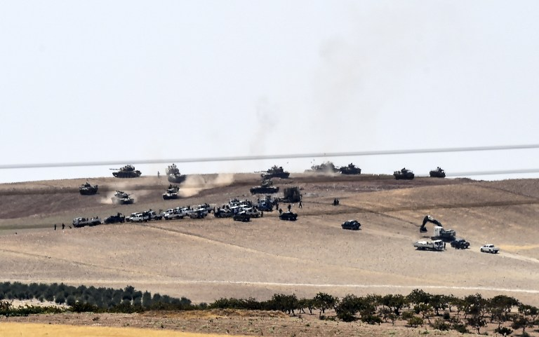 An image taken taken along Turkey's border city of Karkamis on August 24, 2016 shows Turkish army tanks and pro-Ankara Syrian opposition fighters moving two kilometers west from the Syrian town of Jarabulus. (AFP PHOTO/BULENT KILIC)