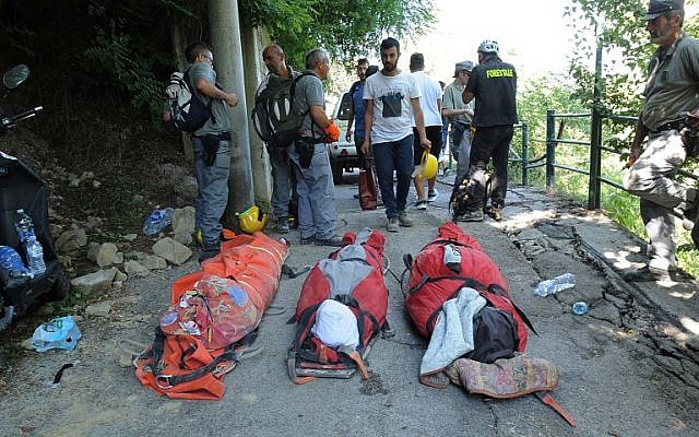 Bodies of victims lie in front of rescuers in the Italian central town of Pescara del Tronto, on August 24, 2016, after a powerful earthquake rocked central Italy. (AFP PHOTO/MARCO ZEPPETELLA)