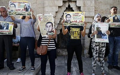 Palestinian protesters hold posters during a demonstration against administrative detention and in support of Palestinian prisoner Bilal Kayed (portraits) on August 24, 2016 at Damascus Gate, a main entrance to Jerusalem's Old City. (AFP PHOTO / AHMAD GHARABLI)