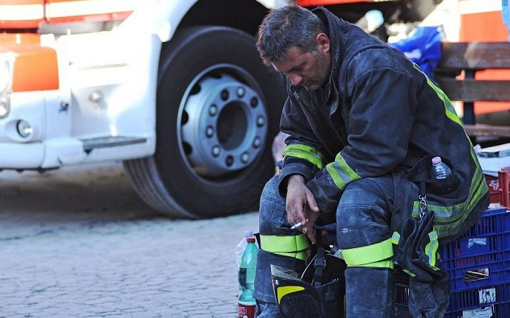A firefighter takes a rest in the central Italian village of Amatrice, on August 24, 2016 after a powerful earthquake rocked central Italy, killing at least 120 people. (AFP PHOTO/MARCO ZEPPETELLA)