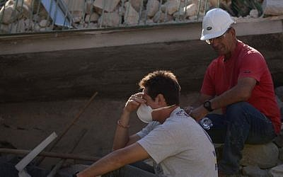 Volunteers pause to rest during search and rescue operations in Amatrice on August 24, 2016 after a powerful earthquake rocked central Italy.  (AFP PHOTO / FILIPPO MONTEFORTE)