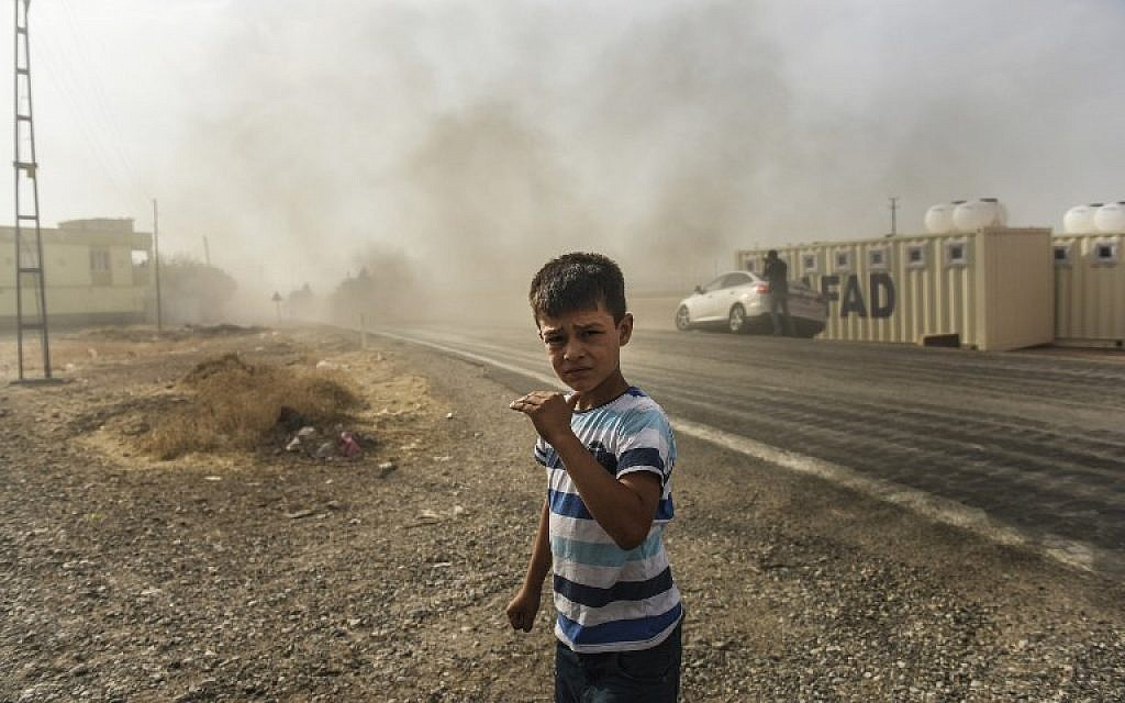 This picture, taken around 5 kilometers west of the Turkish Syrian border city of Karkamis in the southern region of Gaziantep, on August 25, 2016, shows a boy looking on as Turkish Army tanks drive to the Syrian Turkish border town of Jarabulus. (AFP PHOTO / BULENT KILIC)