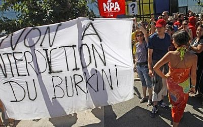 "People, gathered for New Anti-Capitalist Party (NPA) summer meeting, hold a banner reading ""Against forbidding the wearing of the burkini"" as they march in front of Port-Leucate city hall to protest against the municipal ban forbidding the wearing of Burkinis, on August 25, 2016. (Raymond Roig/AFP)"