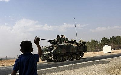 A Turkish boy waves to Turkish tank convoy driving into Syria from the Turkish Syrian border city of Karkamis in the southern region of Gaziantep, on August 26, 2016. AFP  / BULENT KILIC)