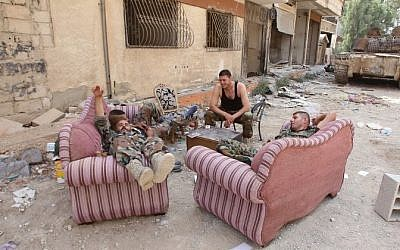 Syrian army soldiers sit on furniture placed in the street in the government-controlled part of the besieged town of Daraya on August 26, 2016, as thousands of rebel fighters and civilians prepared to evacuate. (AFP PHOTO/Youssef KARWASHAN)