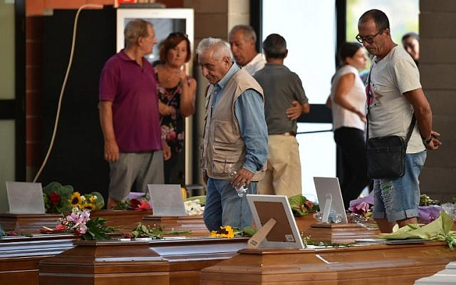 People walk past the coffins of earthquake victims, in a gymnasium arranged in a chapel of rest on August 26, 2016, in Ascoli Piceno, two days after a 6.2-magnitude earthquake struck the region killing 281 people. (AFP PHOTO/ALBERTO PIZZOLI)
