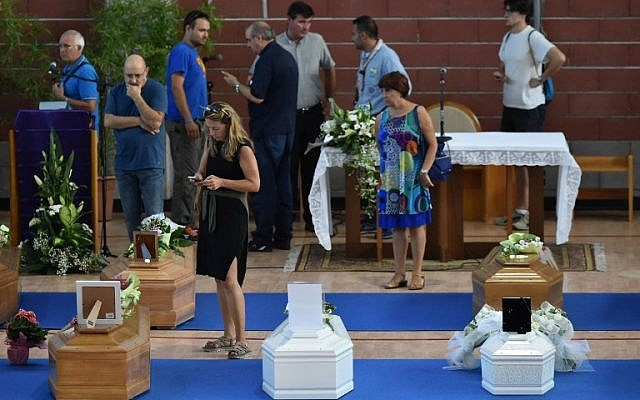 People stand next to the coffins of earthquake victims, in a gymnasium arranged in a chapel of rest on August 26, 2016, in Ascoli Piceno, two days after a 6.2-magnitude earthquake struck the region killing 281 people. (AFP PHOTO/ALBERTO PIZZOLI)
