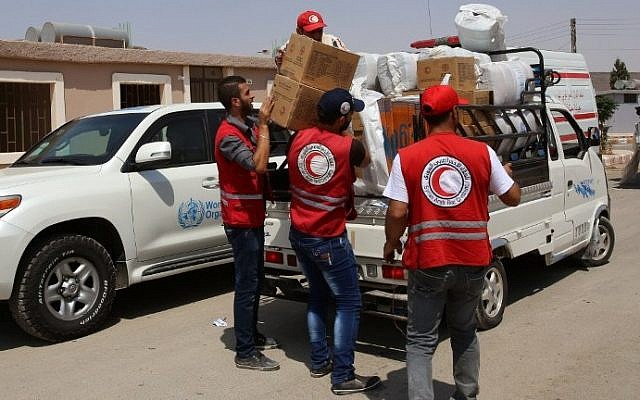 Members of the Syrian Arab Red Crescent (SARC) distribute food parcels at a government reception center in the government-held town of Hrajela in Western Ghouta, outside Damascus, upon the arrival of the families who have been evacuated from the town of Daraya, August 27, 2016. (AFP/Youssef KARWASHAN)