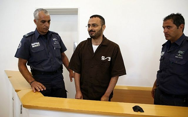 Palestinian Waheed Borsh (C), a UN Development Programme employee in Gaza who is accused of aiding the terror group Hamas, looks on during his indictment at Beersheba District Court on August 28, 2016. (AFP PHOTO/AHMAD GHARABLI)
