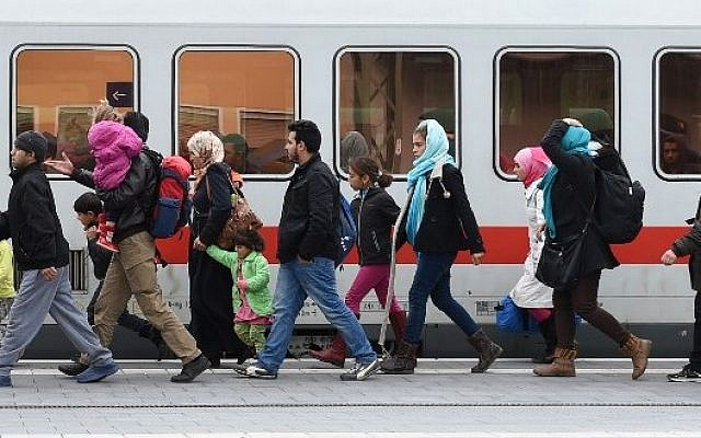 This file photo taken on November 18, 2015, shows migrants walking to a train at the central railway station in Passau, Germany. (AFP Photo/Chirstof Stache)