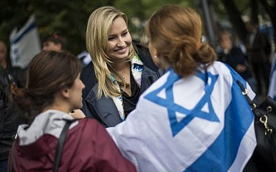 Illustrative: Ebba Busch Thor (C), head of the Christian Democratic Party in Sweden, is greeted by an Israel-flag-draped woman during a 'Taking Back Zionism' pro-Israel rally at Raoul Wallenberg Square in Stockholm on August 28, 2016. (AFP PHOTO/JONATHAN NACKSTRAND)