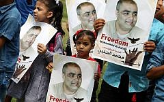 Palestinian children hold posters of Mohammed el-Halabi, left, the Gaza director of World Vision, a major US-based Christian NGO, during a protest to support him at Rafah town in the southern Gaza Strip August 29, 2016. (AFP/SAID KHATIB)