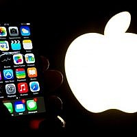Illustrative. A hand holds an iPhone next to the Apple logo (AFP PHOTO / Philippe HUGUEN)