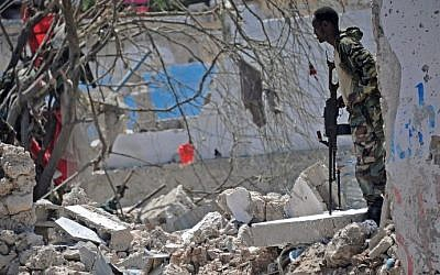 A member of Somalia's security services patrols the scene of a suicide car bomb blast on August 30, 2016 in Mogadishu, Somalia. (AFP PHOTO / Mohamed ABDIWAHAB)