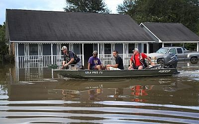 People navigates a boat past a flooded home in Baton Rouge, Louisiana, August 15, 2016. (Joe Raedle/Getty Images/AFP)