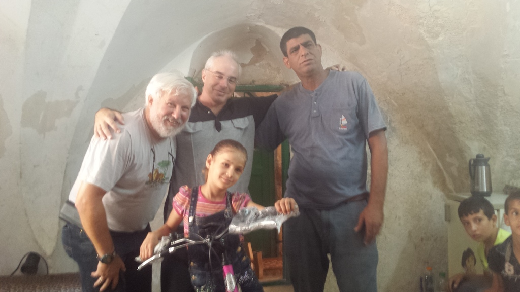 From left to right, Lonny Baskin, Phil Saunders and Ziad Sabateen pose for a picture with 8-year-old Anwar Burqan, whose bicycle was destroyed by two border guards in Hebron, on August 17, 2016. (Lonny Baskin)